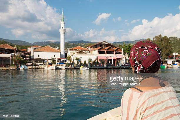 Girl watching Kekova harbour and mosque from a boat in Lycia, Southern Turkey