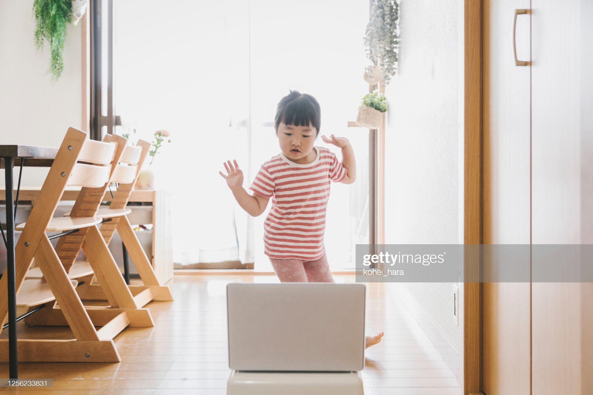 女孩看筆記型電腦和跳舞在家裡 : 圖庫照片