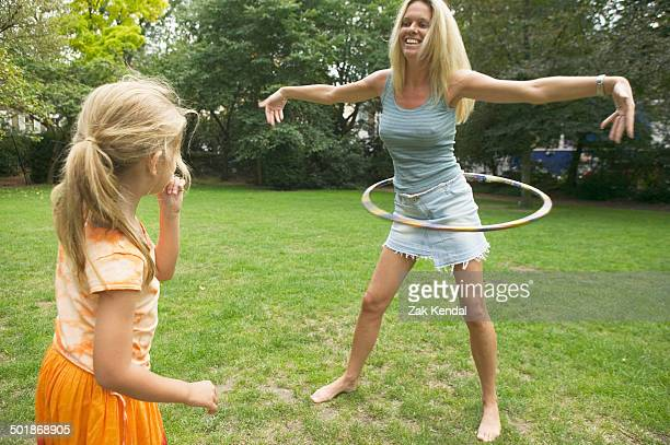 Girl watching mother hula hooping