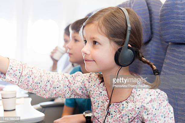 Girl watching movie with headphones on airplane