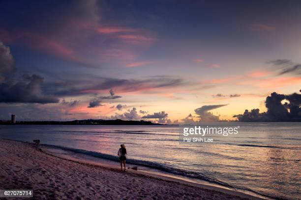 a girl watching sunset at the guam beach - guam stock pictures, royalty-free photos & images
