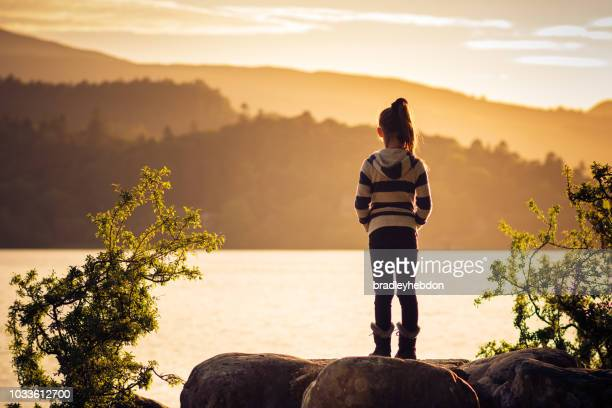 Girl watching sunset over Lake Derwentwater near Keswick, England