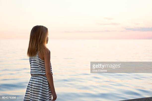 Girl (9-10) watching sunset over water