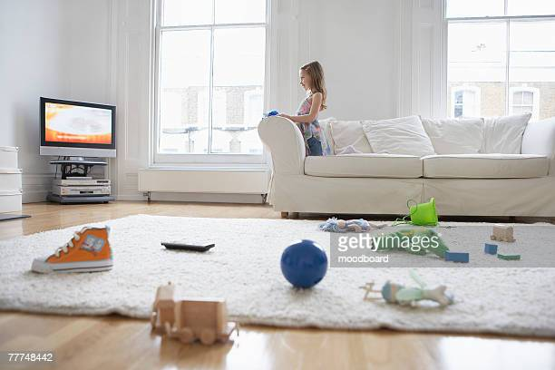 Girl Watching Television in Messy Living Room
