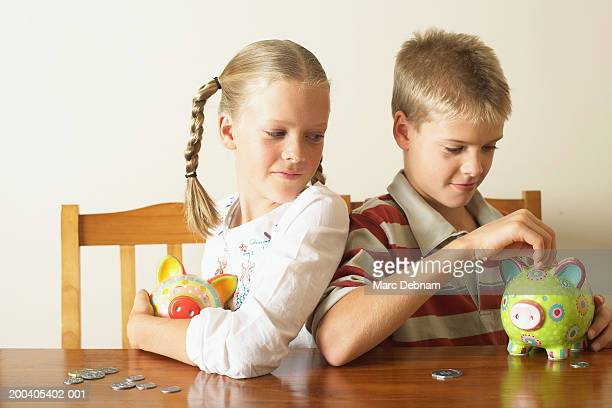 Mädchen (10-12) vor zwei Bruder drop Münze in Sparschwein