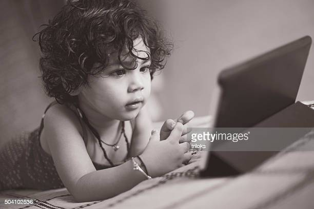 Girl watching video with a digital tablet in home