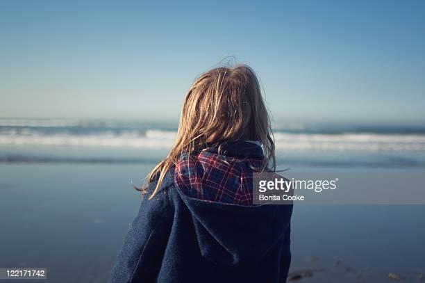 Girl watching waves at winter beach