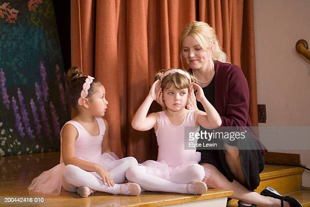 girl (4-6) watching woman style ballerina's (5-7) hair on stage - little girls dressed up wearing pantyhose stock photos and pictures