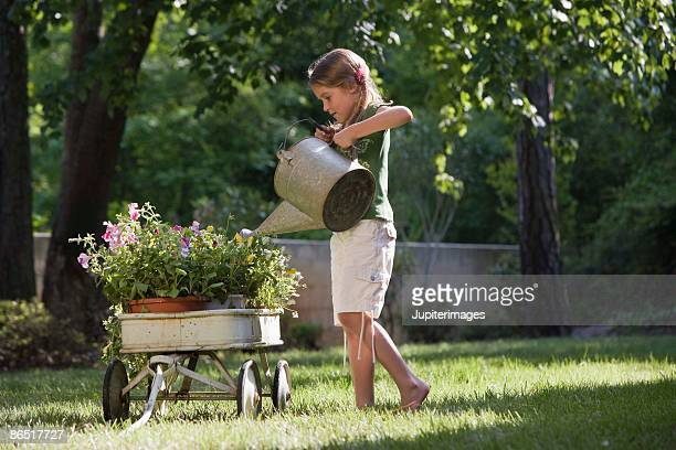 girl watering flowers - toy wagon stock photos and pictures