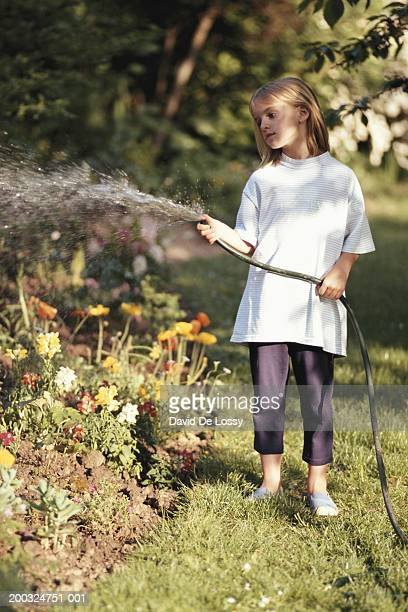 Girl (6-7) watering flowers with hose, standing