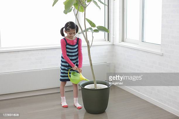 A girl watering pot plant