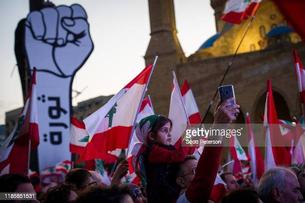 Girl waves a flag as thousands of Lebanese protesters rally against sectarian government and call for the removal of the country's entire political...