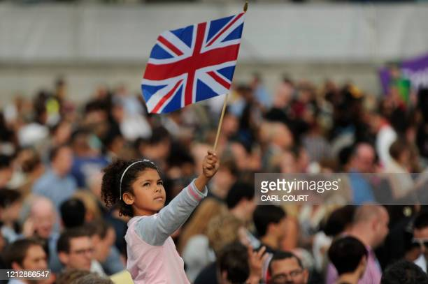 A girl waves a Union Jack flag in Trafalgar Square as the London 2012 gold silver and bronze medals are shown for the first time to mark the oneyear...