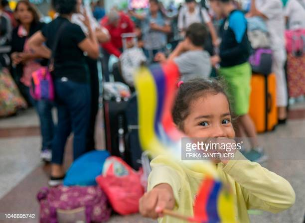 A girl waves a Venezuelan flag at the Santo Domingo airport waiting to return to her country on October 6 2018 A group of about 80 Venezuelans who...