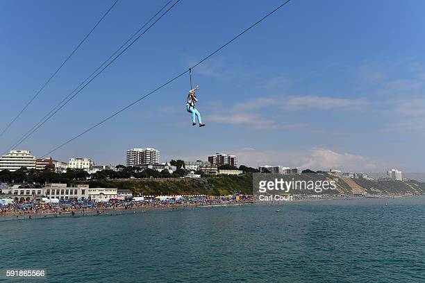 A girl waves from a zipline as people relax on the beach during the Bournemouth Air Festival on August 18 2016 in Bournemouth England The air show...