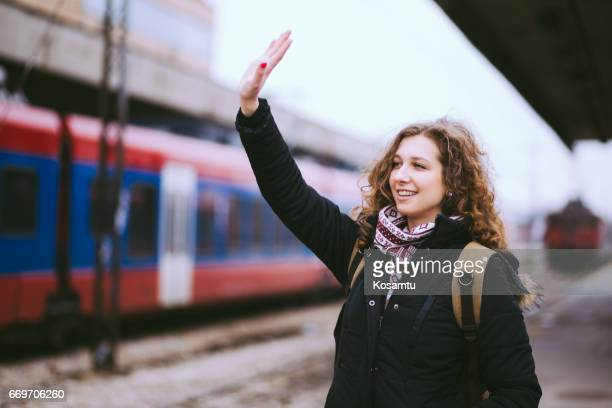 girl waving from railroad station platform - waving gesture stock photos and pictures