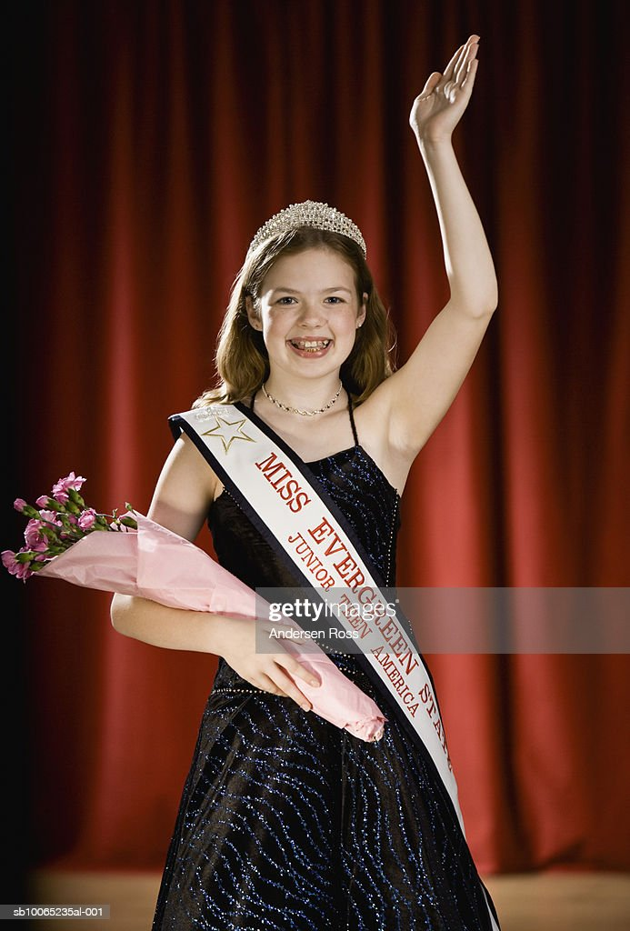 Girl (11-13) waving on stage with bouquet of flowers in beauty pageant : Stock Photo