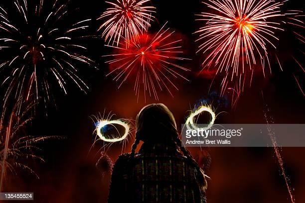 Girl waving sparklers watches firework display