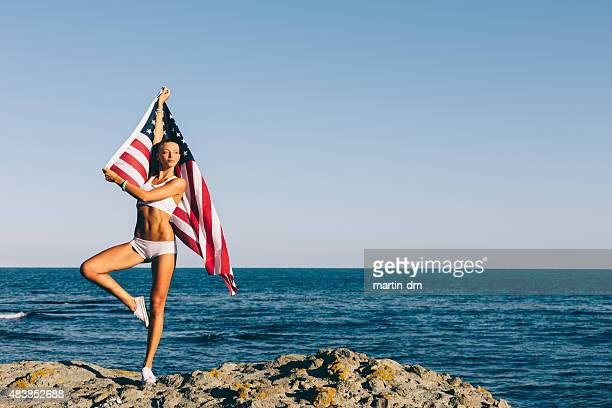 Girl waving the american flag on a rocky beach
