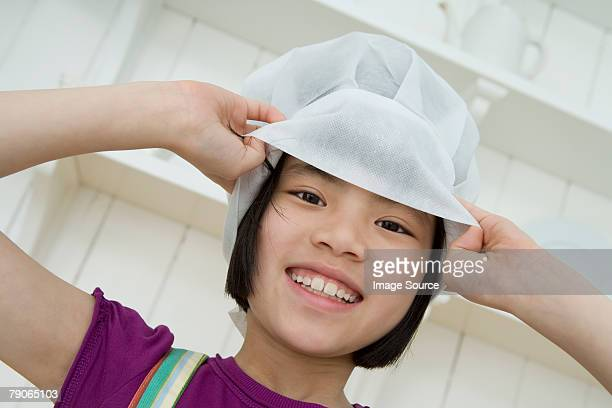 A girl wearing a chefs hat