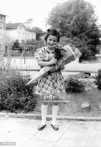 Girl wearing a dress and holding a large school cone and flowers posing for a picture first day at school Germany 1955