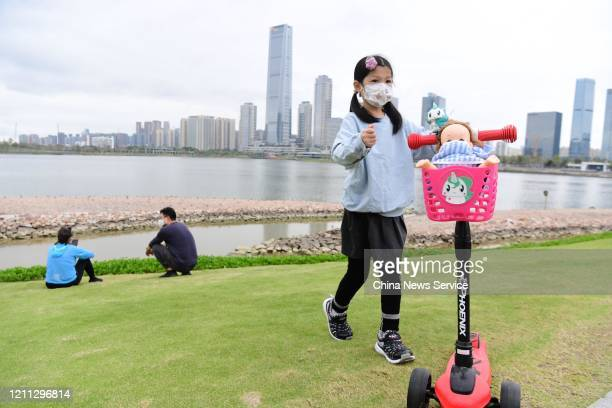 A girl wearing a face mask stands behind a scooter carrying a masked doll at Shenzhen Talent Park on March 8 2020 in Shenzhen Guangdong Province of...