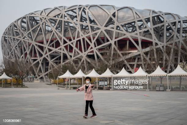 Girl wearing a facemask, amid concerns of the COVID-19 coronavirus, plays at the Olympic park outside the national 'Birds Nest' stadium , the site of...