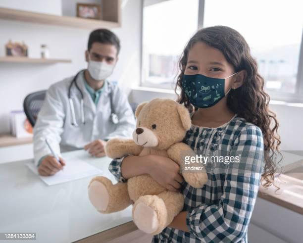 menina usando uma máscara facial em uma consulta médica enquanto segurava um ursinho de pelúcia - pediatra - fotografias e filmes do acervo