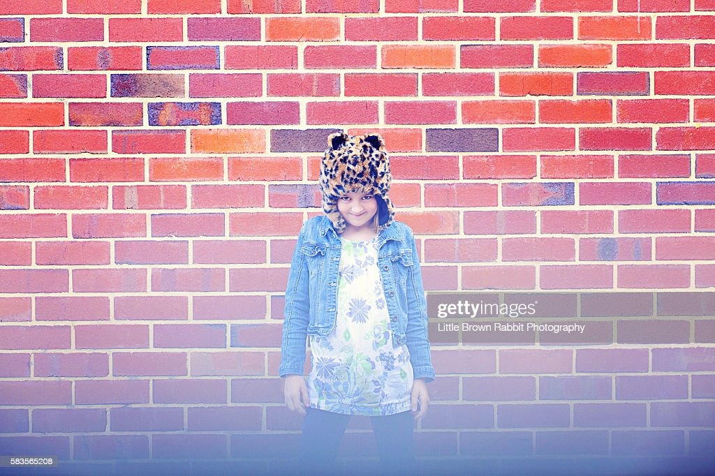Girl Wearing a Hat Against A Brick Wall : Stock Photo