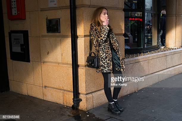 Girl wearing a leopard print fur coat smoking a cigarette while she waits in Leicester Square in London England United Kingdom Her stytlish look...