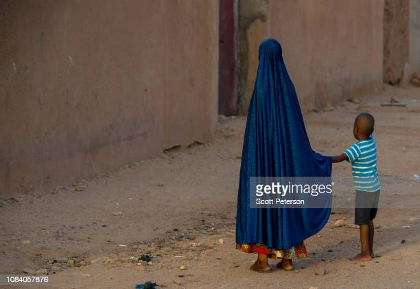 Girl wearing a long blue Islamic gown holds the hand of a boy, as Nigeriens struggle to cope with the challenges of daily life in the second-poorest...