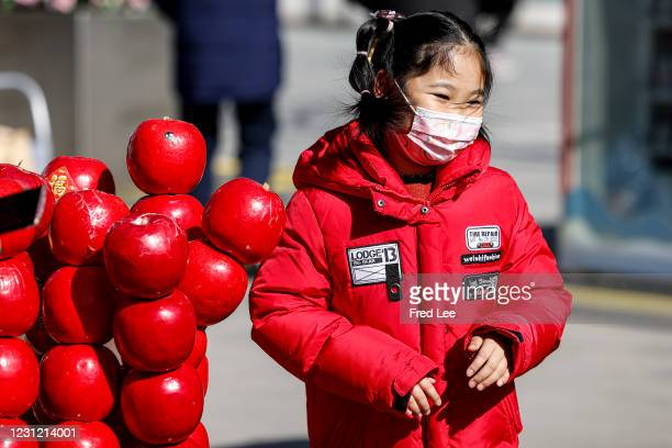 Girl wearing a mask face walks in the Wangfujing Street ahead of Chinese New Year, the Year of the Ox, on February 17, 2021 in Beijing, China.Native...