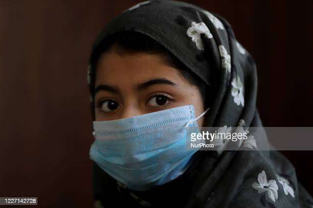 Girl wearing a mask looks on in Sopore town of district baramulla, jammu and Kashmir, India on 15 July 2020