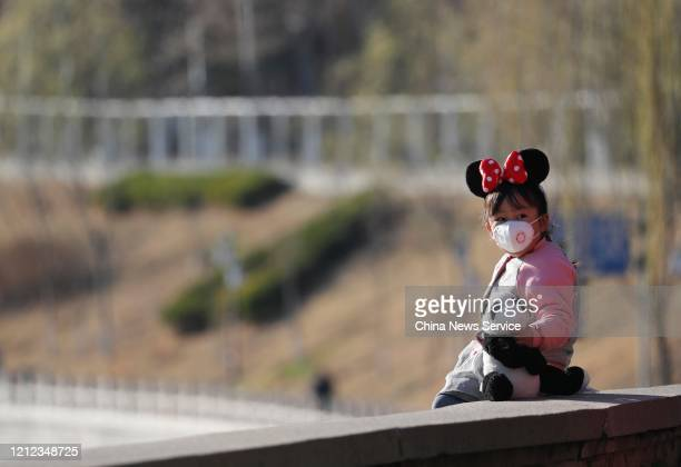 A girl wearing a mask visits Yuyuantan Park amid the coronavirus outbreak on March 13 2020 in Beijing China