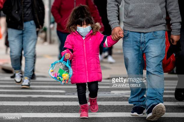 Girl, wearing a mask, walks down a street in the Corona neighborhood of Queens on April 14, 2020 in New York City. - New York will start making tens...