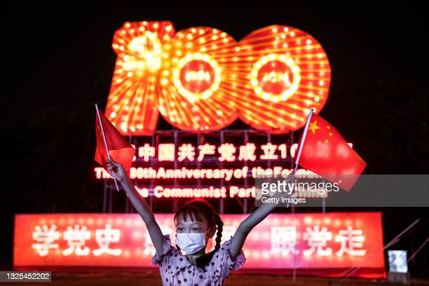 Girl wearing a mask whilst waving the national flag during the centenary of the founding of the CPC history lantern show at Expo Garden on June 25,...