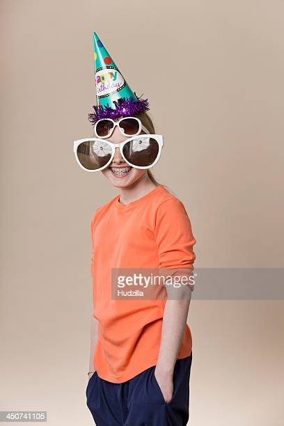 A girl wearing a pair of large novelty sunglasses, a normal pair of sunglasses and a party hat