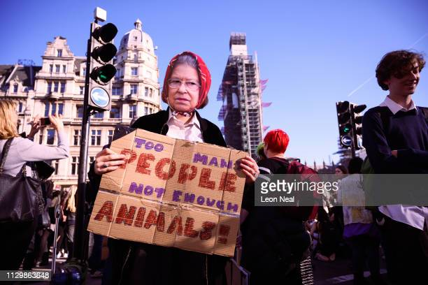 A girl wearing a paper mask of Britain's Queen Elizabeth II joins a climate protest in Parliament Square on February 15 2019 in London United Kingdom...