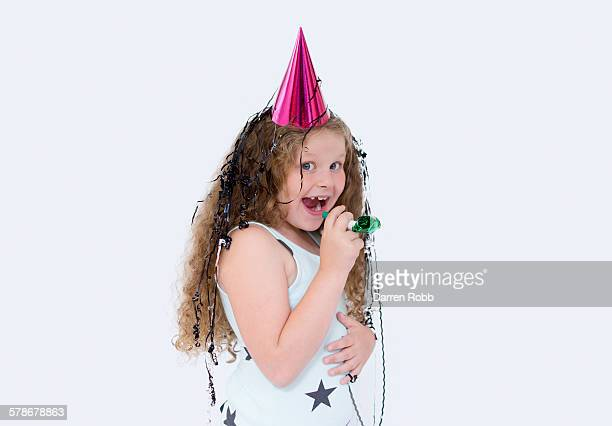 Girl wearing a party hat holding a party blower