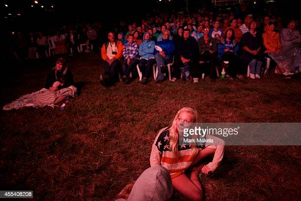 A girl wearing a patriotic shirt with face painting watches a monitor during a during a fireworks display commemorating the bicentennial of the...