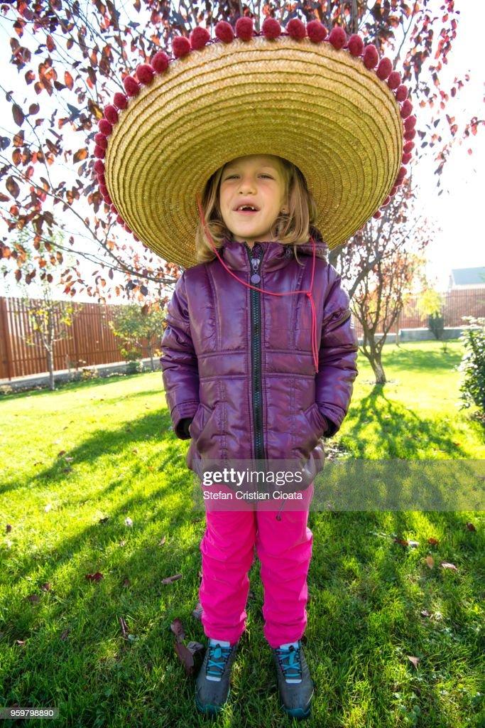 Girl wearing a sombrero in backyard : Stock-Foto