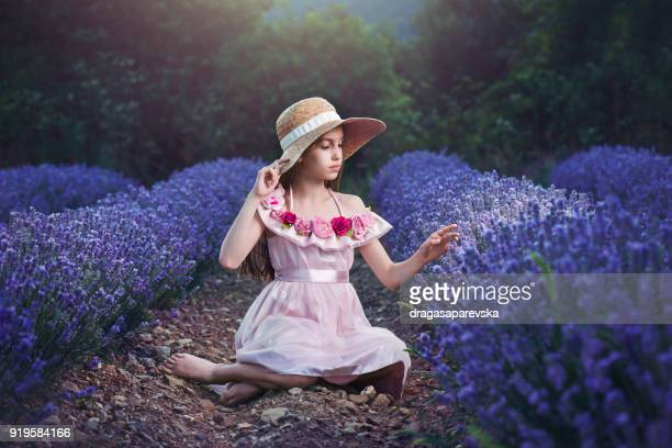 Girl wearing a straw hat sitting in a lavender field