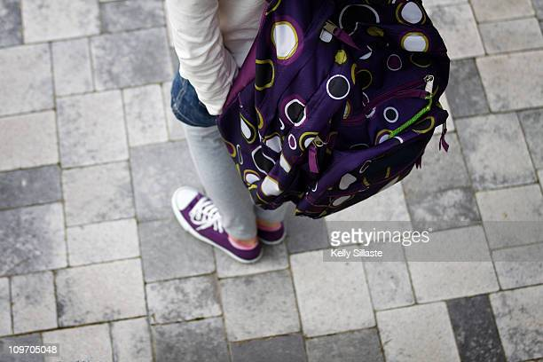 A girl wearing a stylish purple polka-dot backpack