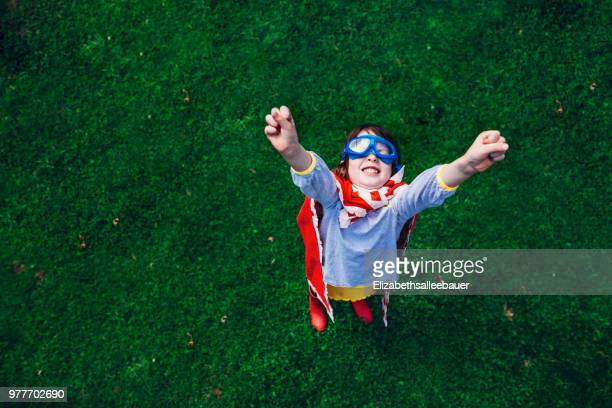 girl wearing a superhero costume standing in the garden with her arms in the air - super stock pictures, royalty-free photos & images