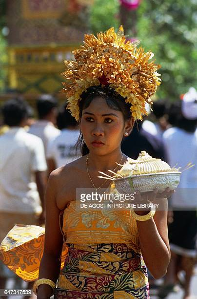 Girl wearing a traditional costume during a religious procession bringing an offering Bali Indonesia