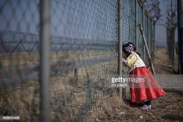 A girl wearing a traditional hanbok dress stands at a military fence facing towards North Korea at Imjingak park south of the Military Demarcation...