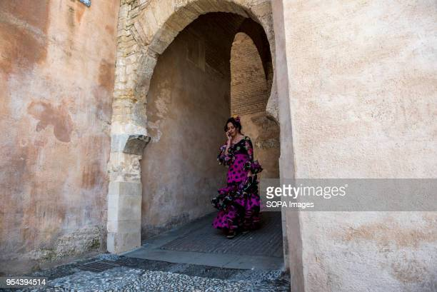 A girl wearing a typical flamenco dress walking throught the gate of Arco de las Pesas El día de la Cruz or Día de las Cruces is one of the most...