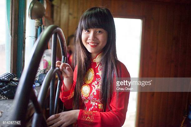 Girl wearing a Vietnamese traditional dress called Ao Dai getting ready for an wedding on a boat in Nguyet Duc floating village Bac Ninh province...