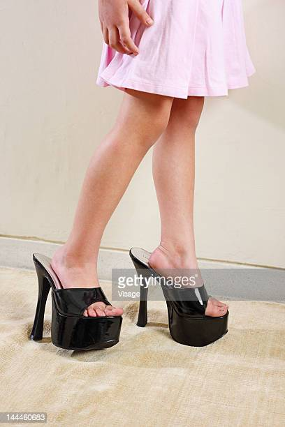 girl wearing an woman's sandals - little girl in high heels stock photos and pictures