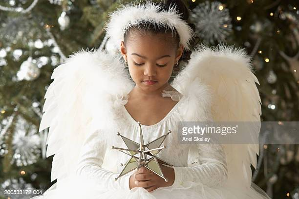 Girl (5-6) wearing angel costume, holding star, Christmas tree in background